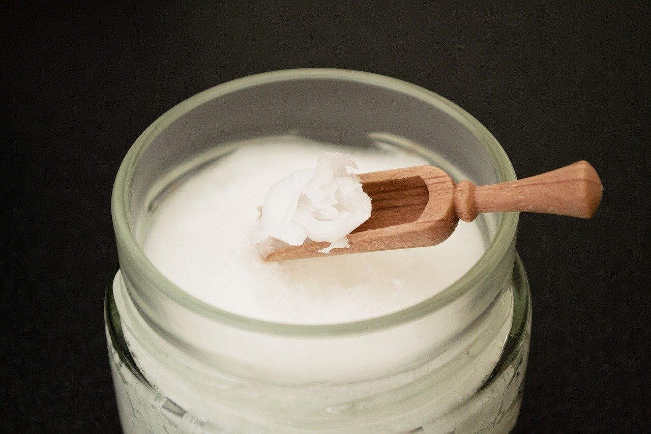 coconut oil in a jar with a wooden spoon